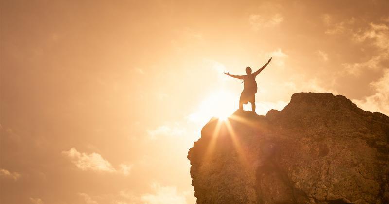 Image of man on top of a mountain by kierferpix via Adobe Stock.