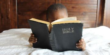 Child reading the bible. Image via pixabay